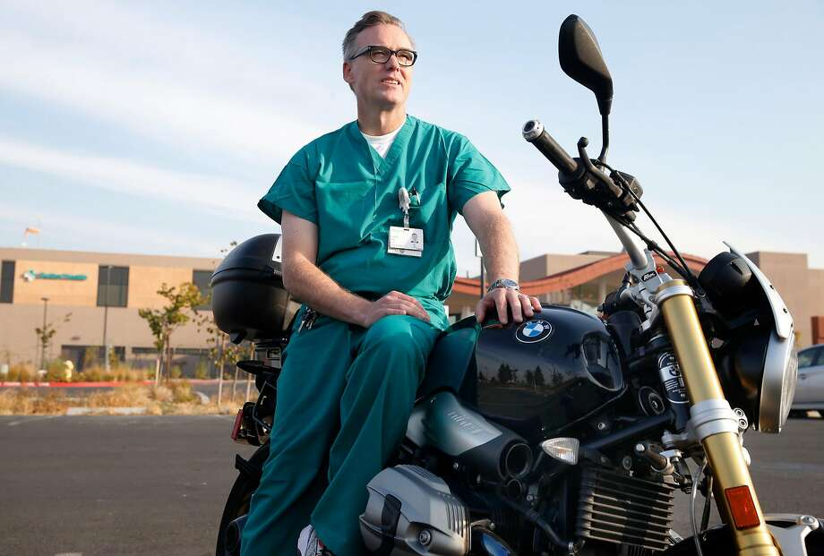 Neonatal physician Dr. Scott Witt of Sutter Santa Rosa Regional Hospital sits on the BMW motorcycle he rode through fiery streets to rescue infants as flames advanced on the hospital. Photo: Paul Chinn, The Chronicle