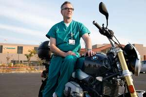 Neonatal physician Dr. Scott Witt sits on his BMW motocycle in the parking at Sutter Santa Rosa Regional Hospital which resumed full operations in Santa Rosa, Calif. on Tuesday Oct. 17, 2017. Witt rode his motorcycle to the hospital through last week's firestorm to direct the evacuation of eight neonatal patients despite losing his Fountaingrove home in the process.