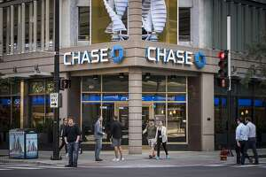 Pedestrians pass in front of a JPMorgan & Chase bank branch in downtown Chicago, Illinois, U.S., on Monday, Oct. 9, 2017. JPMorgan Chase & Co. is scheduled to release earning figures on October 12. Photographer: Christopher Dilts/Bloomberg