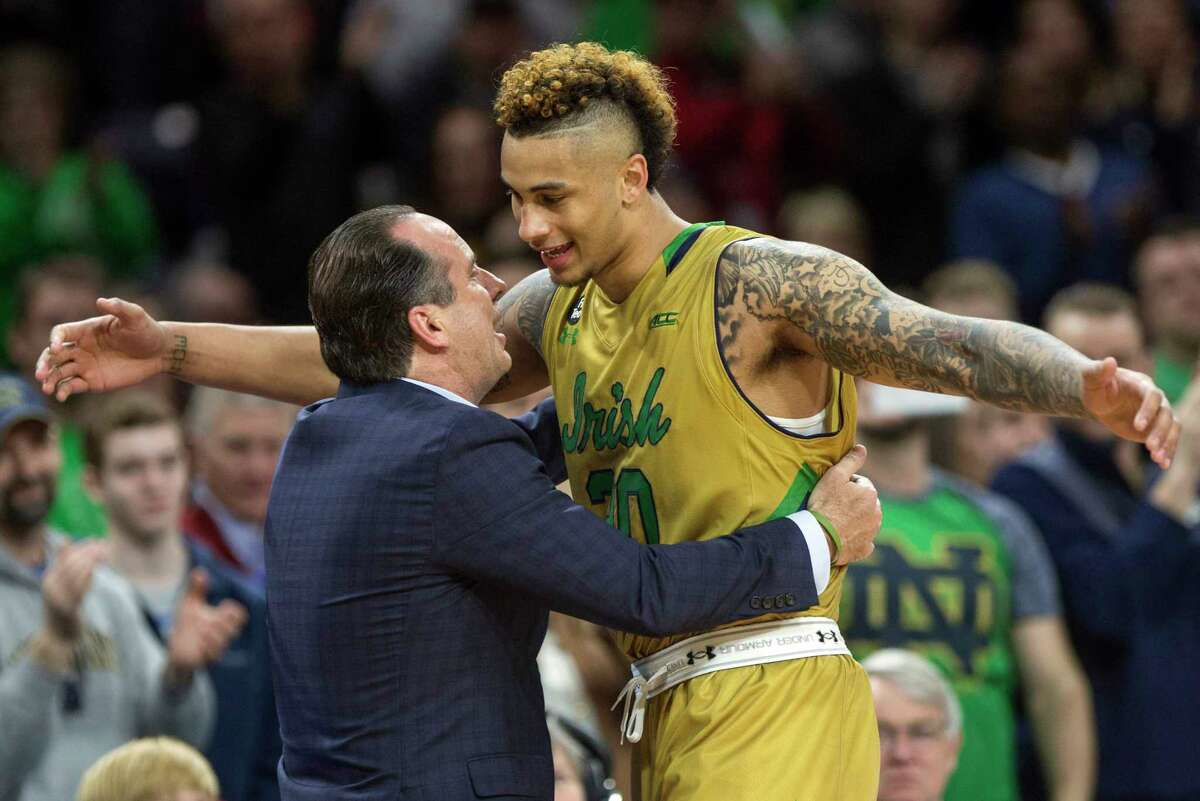 Notre Dame's Zach Auguste (30) hugs head coach Mike Brey as he comes off the court for the final time on Senior Day during the second half of Notre Dame's 89-75 win against North Carolina State in an NCAA college basketball game Saturday, March 5, 2016, in South Bend, Ind.