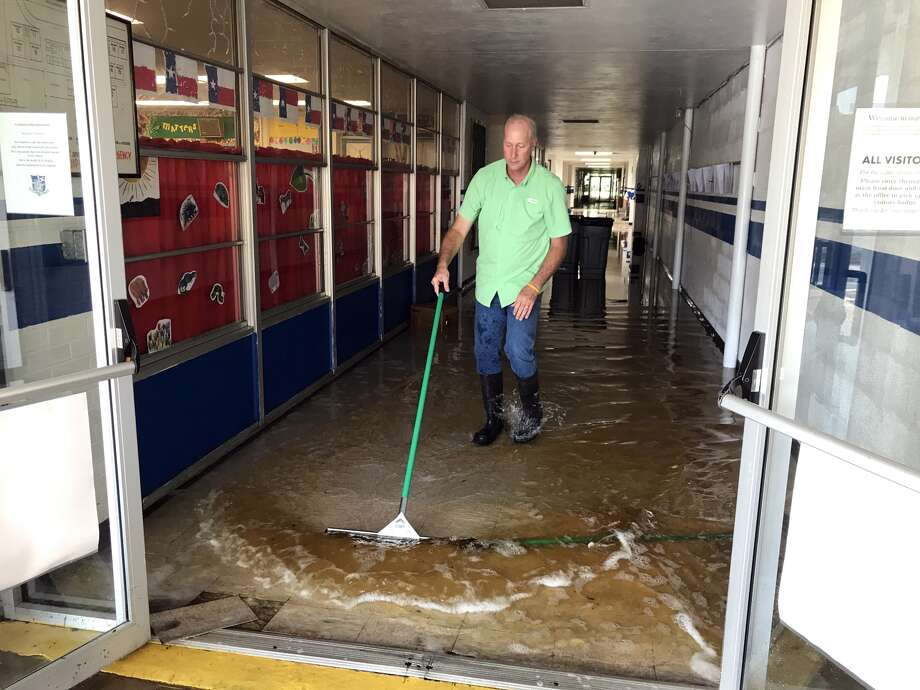 Workers at St. Catherine of Siena Catholic School in Port Arthur clean up after the remnants of Hurricane Harvey passed over Southeast Texas in late August, flooding the school.