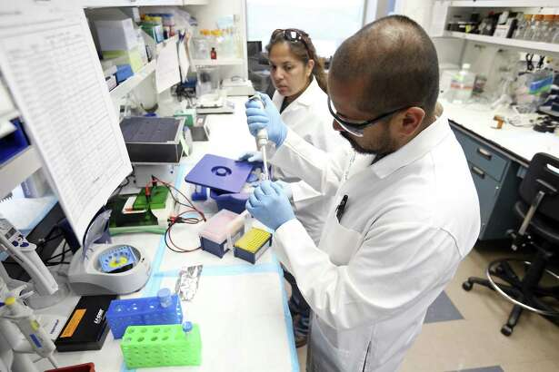 University of Texas Health Science Center at San Antonio Graduate School of Biomedical Sciences student Anthony Martinez (right) and UTHSC laboratory technician Vanessa Martinez work on a Western blot technique at the Sam and Ann Barshop Institute for Longevity and Aging Studies in this 2016 file photo. The center is now called UT Health, and it broke ground Thursday on a new $70 million facility for the institute.