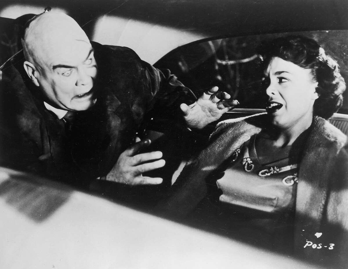 Swedish-born actor Tor Johnson attacks actor Mona McKinnon in the back seat of an automobile in a still from director Ed Wood's film