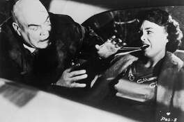 Swedish-born actor Tor Johnson attacks actor Mona McKinnon in the back seat of an automobile in a still from director Edward D. Wood Jr.'s film 'Plan 9 from Outer Space.'  Johnson, who has a zombie expression, holds his hands outstretched.   (Photo by Hulton Archive/Getty Images)