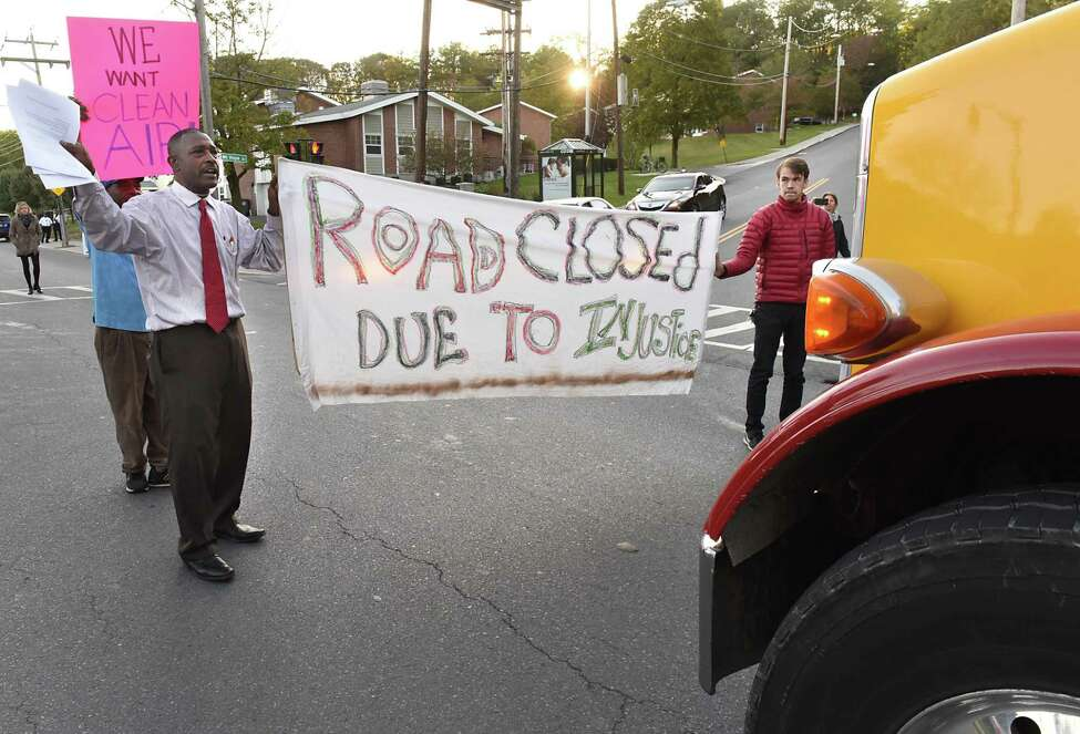 Willie White, executive director of AVillage, left, and protestor Sean Collins, right, stand in the middle of South Pearl St. and block a diesel truck from driving by the Ezra Prentiss homes on Tuesday, Oct 17, 2017 in Albany, N.Y. The truck nearly ran over the protestors at a slow speed. They were protesting diesel trucks polluting the air as they drove past the homes and want them to be re-routed. (Lori Van Buren / Times Union)