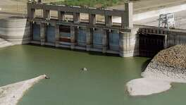 The low level of the reservoir at Falcon Dam, one of two reservoirs on the Rio Grande, Wednesday, May 15, 2001 in Harlingen, Texas.  The water level is now below the flood gate doors, and visitors can stand at what used to be the bottom of a deep lake; two cities covered by the lake waters in the 1950's have emerged during the drought.   CHRISTOBAL PEREZ/HOUSTON CHRONICLE.  HOUCHRON CAPTION  (05/19/2002):  The water at Falcon Dam, one of two reservoirs on the Rio Grande River, is now below the floodgate doors, and visitors can stand at what used to be the bottom of a deep lake.     HOUCHRON CAPTION (04/10/2005) SECMETRO:  DROUGHT ENDING:  This 2001 photo shows Falcon Lake below the floodgates.  It is now about 64 percent full.