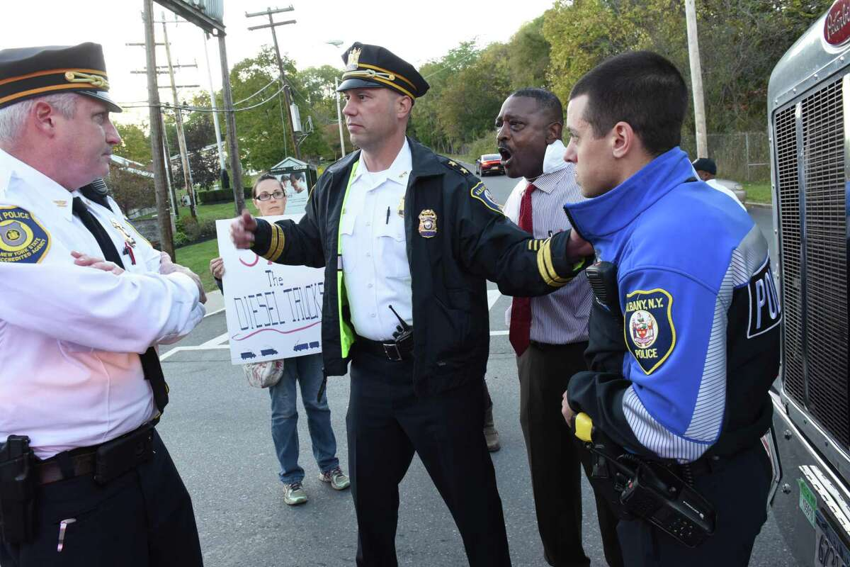 Police talk to Willie White, executive director of AVillage, second from right, as he stands in the middle of South Pearl St. and blocks a diesel truck from driving by the Ezra Prentiss homes on Tuesday, Oct 17, 2017 in Albany, N.Y. People were protesting diesel trucks polluting the air as they drove past the homes and want them to be re-routed. (Lori Van Buren / Times Union)