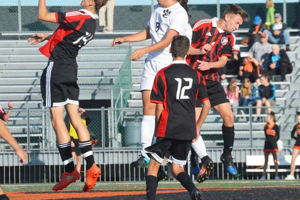 Edwardsville midfielder Devin Parker, center, wins a 50-50 ball with a header against three Granite City defenders during first-half action of the Class 3A Edwardsville Regional semifinals inside the District 7 Sports Complex on Tuesday.