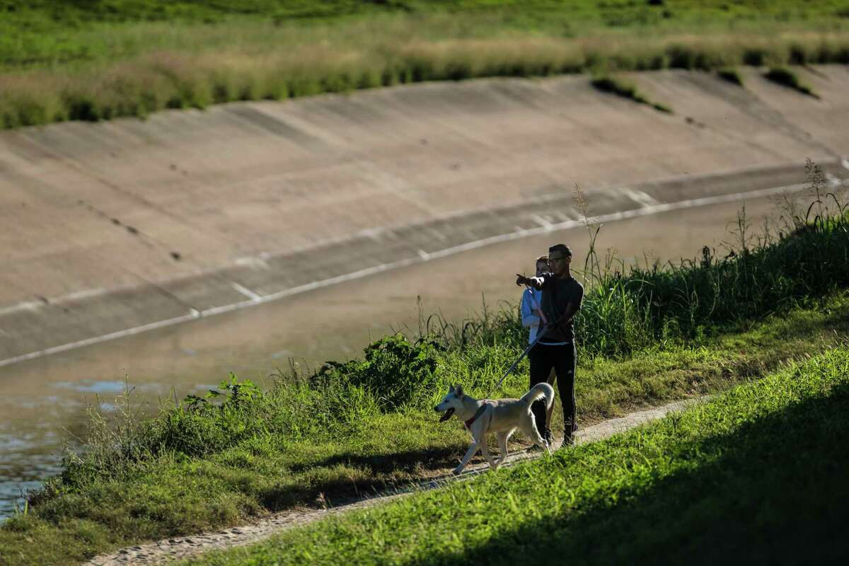 Ricardo Estrada, 26, and Erika Ramirez, 24, walk Blue by the White Oak Bayou, Tuesday, Oct. 17, 2017, in Houston. The couple thinks the bayou would look better if the concrete around it be removed.