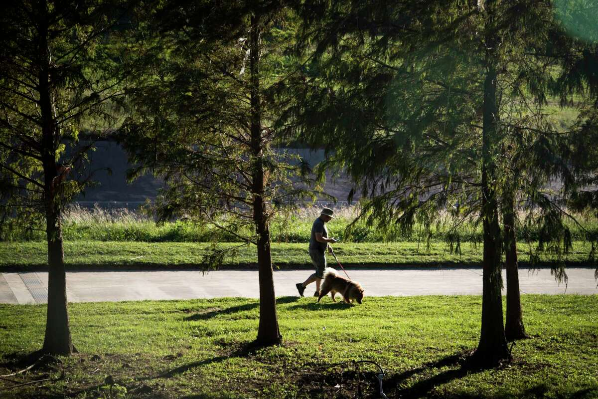 A man walks his dog by the White Oak Bayou, Tuesday, Oct. 17, 2017, in Houston.