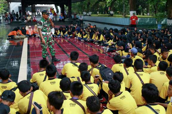 On Sunday, an army officer speaks to school children to explain the details of the Pancasila Sakti Monument which was built to commemorate an abortive coup in 1965 that led to the anti-communist purge in 1965-1966.