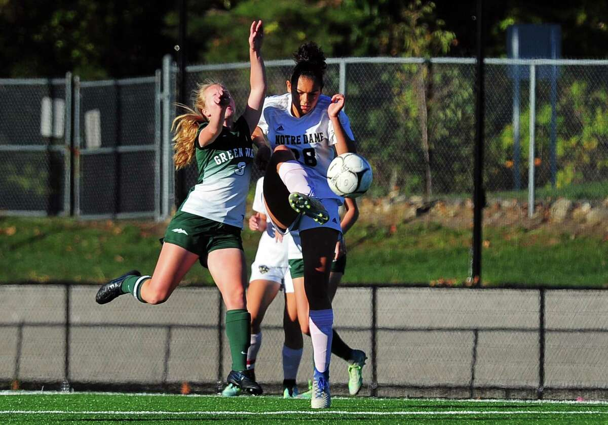 Notre Dame of Fairfield's Jazmine Fred high kicks the ball as New Milford's Sarah Marsan intercepts during girls soccer action in Fairfield, Conn., on Tuesday Oct. 17, 2017.