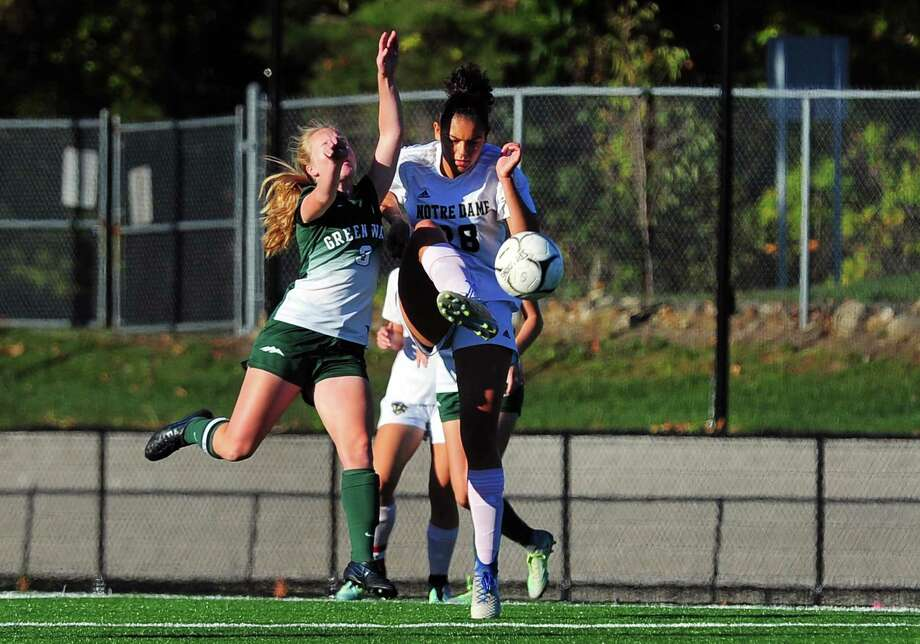 Notre Dame of Fairfield's Jazmine Fred high kicks the ball as New Milford's Sarah Marsan intercepts during girls soccer action in Fairfield, Conn., on Tuesday Oct. 17, 2017. Photo: Christian Abraham / Hearst Connecticut Media / Connecticut Post