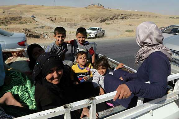 People return back to Kirkuk, 290 kilometers (180 miles) north of Baghdad, Iraq, Tuesday, Oct. 17, 2017. Thousands of civilians are streaming back to Kirkuk, a day after fleeing as Iraqi troops pushed Kurdish forces out of the disputed oil-rich city. (AP Photo/Khalid Mohammed)