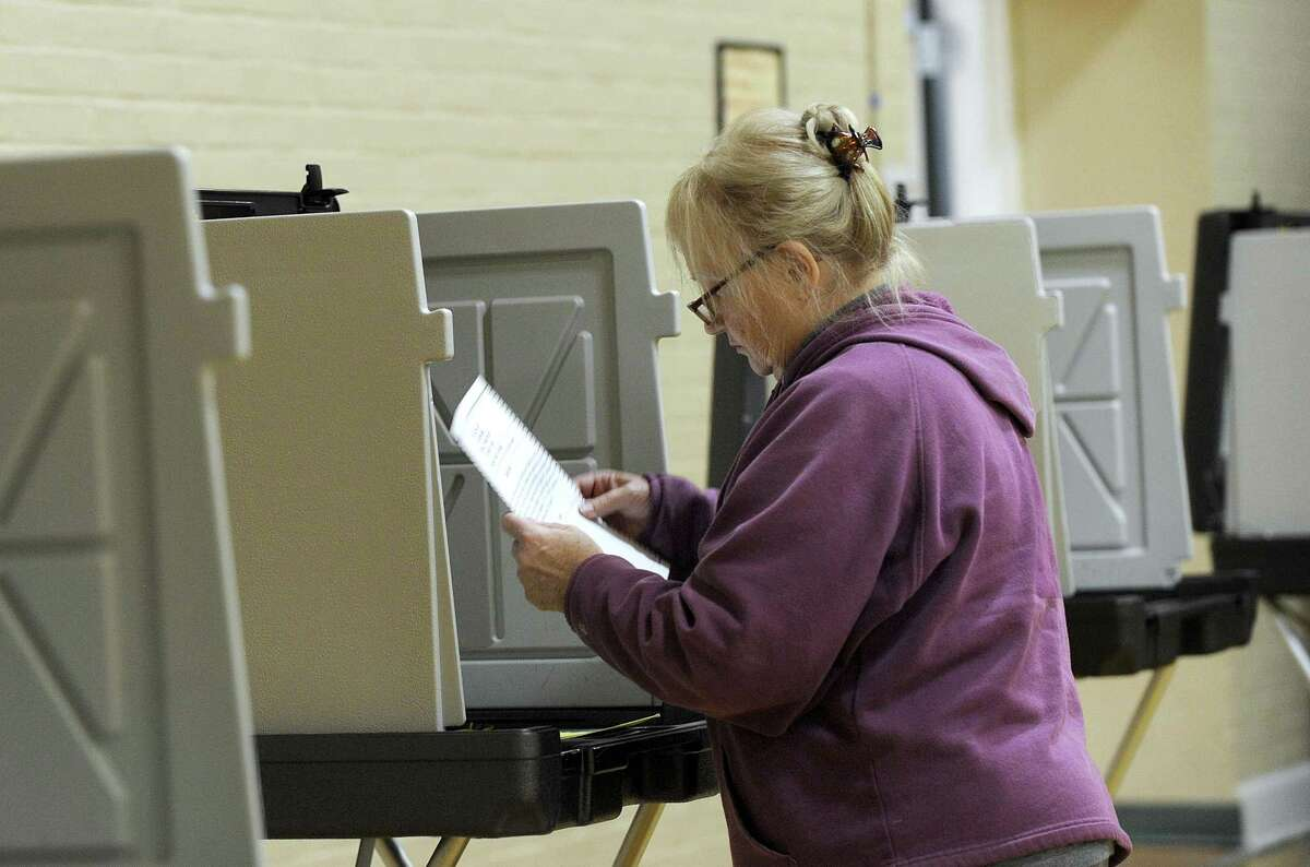 Eileen Abel looks over her ballot before marking her vote at the Municipal Center polling place in Bethel, Tuesday, Oct. 17, 2017. Bethel residents are voting on the $65.8 million elementary school renovation project on Tuesday.