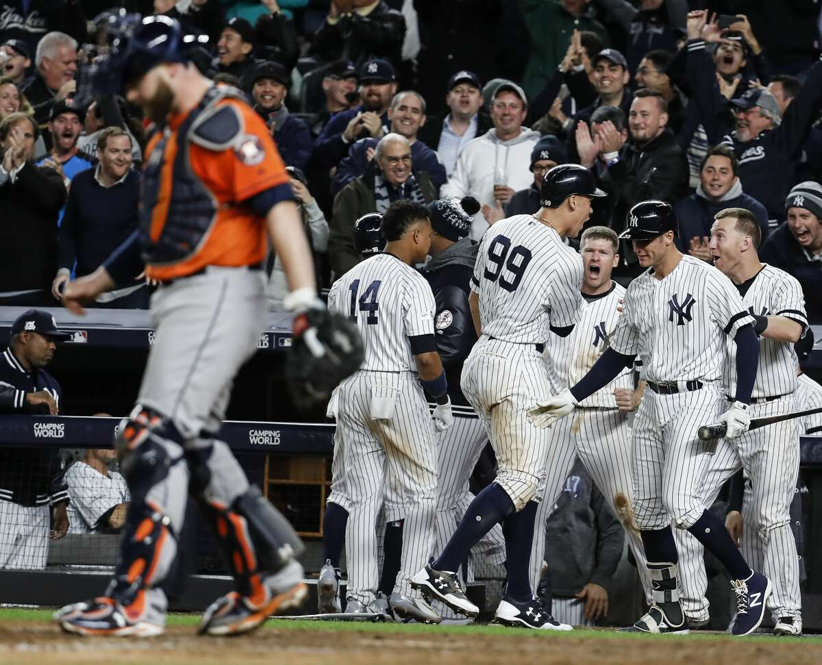 New York Yankees right fielder Aaron Judge (99) and first baseman Greg Bird (33) celebrate after the Yankees scored a pair of runs in the bottom of the eighth inning to take a two-run lead in Game 4 of the ALCS as Houston Astros catcher Brian McCann walks toward the mound at Yankee Stadium on Tuesday, Oct. 17, 2017, in New York. ( Karen Warren / Houston Chronicle )