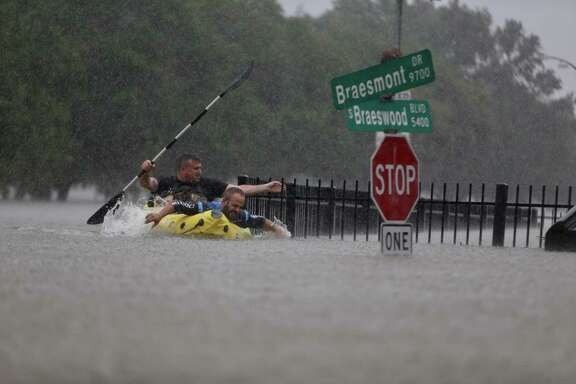 Two kayakers try to beat the current pushing them down an overflowing Brays Bayou along S. Braeswood Sunday, August 27, 2017.(Mark Mulligan / Houston Chronicle)
