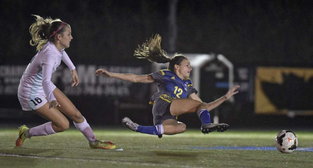 Newtown's Sydney Howard (12) has her feet come out from under her as she beats Immaculate's Kinsey Jarboe (16) in the girls soccer game between Newtown and Immaculate high schools on Tuesday night, October 17, 2017, at Immaculate High School, Danbury, Conn.