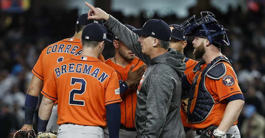 Houston Astros manager A.J. Hinch, center, makes the call to the bullpen during the seventh inning of Game 4 of the ALCS against the New York Yankees at Yankee Stadium on Tuesday, Oct. 17, 2017, in New York. ( Karen Warren  / Houston Chronicle ) Photo: Karen Warren/Houston Chronicle