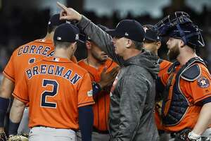 Houston Astros manager A.J. Hinch, center, makes the call to the bullpen during the seventh inning of Game 4 of the ALCS against the New York Yankees at Yankee Stadium on Tuesday, Oct. 17, 2017, in New York. ( Karen Warren  / Houston Chronicle )