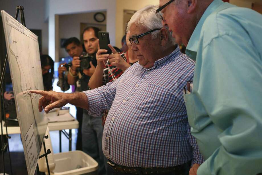 Starr County residents Ruperto Escobar, left, and Alonzo Alvarez review a proposed map of of the U.S.-Mexico border wall during a town hall meeting in Roma, Texas, Tuesday, Oct. 17, 2017. Photo: JERRY LARA / San Antonio Express-News / San Antonio Express-News