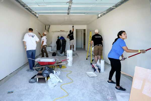 """Wendy Stanley, right, works with a team of volunteers to repair a flood-damaged house, in Houston. """"It's just about giving back,"""" Stanley said. """"Just figuring out how we could help those more affected than we were."""""""