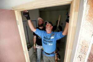 "Rob ""Gator"" Collett, center, a volunteer leader with Habitat for Humanity, hangs a door with the help of Dustin Maples, left, and Brian Thompkins, right rear, Tuesday, Oct. 17, 2017, in Houston."