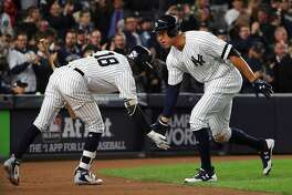 New York Yankees right fielder Aaron Judge, right, celebrates his solo home run with shortstop Didi Gregorius (18) in the 7th inning of Game 4 of the American League Championship Series, at Yankee Stadium in the Bronx, Oct. 17, 2017. The Houston Astros lead the series, 2-1. The Yankees won the game, tying the series 2-2. (Chang W. Lee/The New York Times)