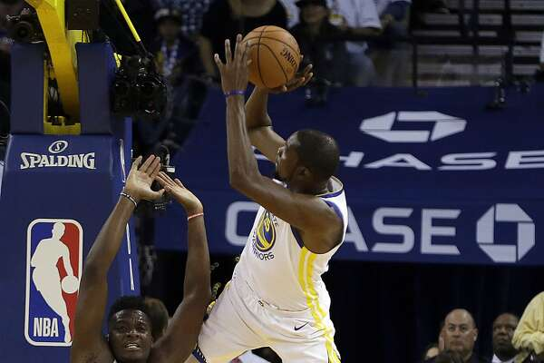 Golden State Warriors' Kevin Durant, right, shoots over Houston Rockets' Clint Capela (15) during the first quarter of an NBA basketball game Tuesday, Oct. 17, 2017, in Oakland, Calif. (AP Photo/Ben Margot)