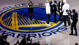 Golden State Warriors guard Stephen Curry (30) is presented with his championship ring by Warriors co-owners Joseph Lacob and Peter Guber during the ring ceremony before an NBA game between the Warriors and the Houston Rockets at Oracle Arena on Tuesday, Oct. 17, 2017, in Oakland, Calif.