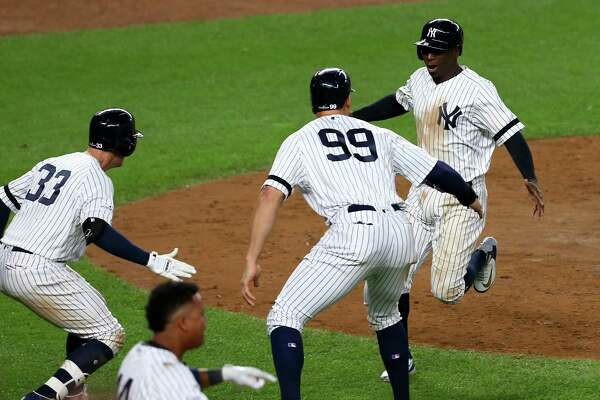 NEW YORK, NY - OCTOBER 17:  Aaron Judge #99 and Didi Gregorius #18 of the New York Yankees celebrate after scoring on a two-run go-ahead double by Gary Sanchez #24 during the eighth inning against the Houston Astros in Game Four of the American League Championship Series at Yankee Stadium on October 17, 2017 in the Bronx borough of New York City.  (Photo by Mike Stobe/Getty Images) ORG XMIT: 775058094