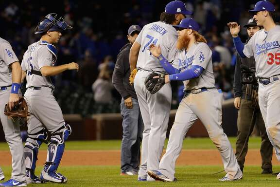 CHICAGO, IL - OCTOBER 17:  (L-R) Logan Forsythe #11, Austin Barnes #15, Kenley Jansen #74, Justin Turner #10 and Cody Bellinger #35 of the Los Angeles Dodgers celebrate defeating the Chicago Cubs 6-1 in game three of the National League Championship Series at Wrigley Field on October 17, 2017 in Chicago, Illinois.  (Photo by Jamie Squire/Getty Images)