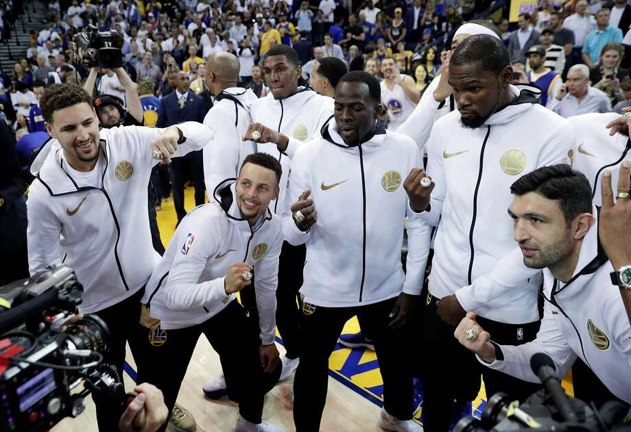 The Golden State Warriors pose with their championship rings before they played the Houston Rockets at Oracle Arena in Oakland, Calif., Tuesday, October 17, 2017. Photo: Carlos Avila Gonzalez, The Chronicle