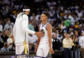 JaVale McGee (1) pats Stephen Curry (30) on on the chest during a timeout in the second half as the Golden State Warriors played the Houston Rockets at Oracle Arena in Oakland, Calif., Tuesday, October 17, 2017.