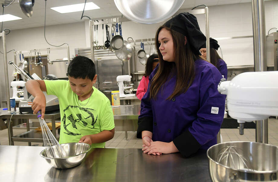 Lemm Elementary 5th grader Jonathan Garcia, 10, left, practices his egg beating  with help from Klein Cain High School sophomore Culinary Arts student Vivian Van Ness, 15, during a mentoring opportunity for the students at Klein Cain High School on Oct. 17, 2017. (Photo by Jerry Baker/Freelance) Photo: Jerry Baker, Freelance / Freelance