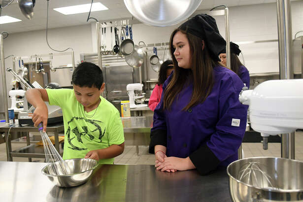 Lemm Elementary 5th grader Jonathan Garcia, 10, left, practices his egg beating  with help from Klein Cain High School sophomore Culinary Arts student Vivian Van Ness, 15, during a mentoring opportunity for the students at Klein Cain High School on Oct. 17, 2017. (Photo by Jerry Baker/Freelance)