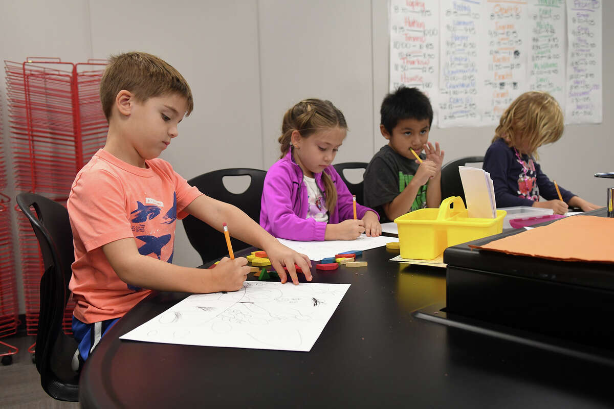 Lemm Elementary kindergartners Evan Mehok. 5, from left, Eva Larmouth, 5, Evan Longoria, 6, and Olivia Cole, 5, work on a 400 lb. slate table in a science room make-shifted into an elementary school art room for art teacher Ashley Campbell at Klein Cain High School on Oct. 17, 2017. (Photoby Jerry Baker/Freelance)