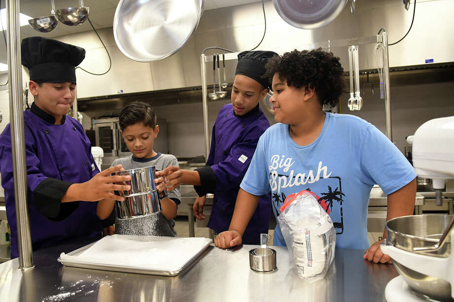 Klein Cain High School sophomore Cody Hendry, 15, from left, helps Lemm Elementary 5th grader Dominic Castillo, 10, with his flour sifting technique while Hendry's classmate JaQuan Louis, 15, and Castillo's classmate Vincent Perdue, 11, back up the pair during a mentoring opportunity for the students at Klein Cain High School on Oct. 17, 2017. (Photoby Jerry Baker/Freelance) Photo: Jerry Baker, Freelance / Freelance