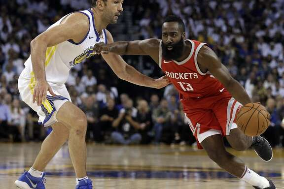 El jugador de los Rockets de Houston James Harden, a la derecha, lleva el balón frente al jugador de los Warriors de Golden State Zaza Pachulia durante el primer cuarto de su juego de baloncesto el martes 17 de octubre de 2017, en Oakland, California. (AP Foto/Ben Margot)