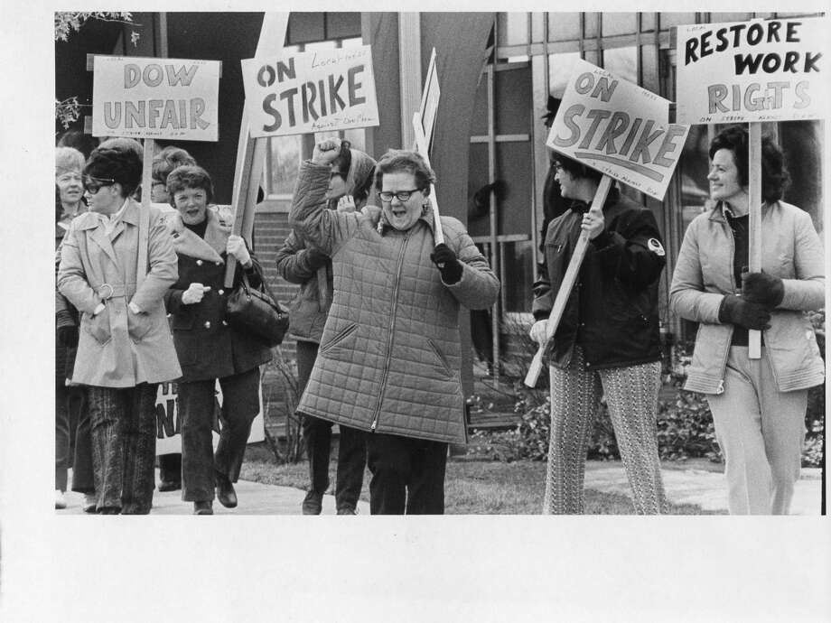A woman salutes a sympathetic trucker, one of many who drove by and tooted their horns to Dow-Bay City strikers. (April 1972)Contract negotiations reach impasse Feb. 6, 1972; Dow three-year contract offer totaled $1.34 per hour in wage and benefit increase. 170 members of Local 14055, United Steelworkers of America, begin strike Feb. 7, 1972. Bay City plants were operated by salaried employees. First striking employees return to work September 1972. Nearly 50 percent of striking employees return to work in March/April 1973. Petition signed by 70 percent of employees informing Dow that employees no longer want Local 14055, United Steelworkers, as their representative on April 13, 1973. Company honors petition and notifies United Steelworkers of withdrawal of recognition on April 16, 1973. Employees changed to all-salaries status. Dow offer extended to remaining strikers providing opportunity for them to reclaim their job or similar job on salary basis. Offer to striking employees expires April 25, 1973; three men responded to offer. (Information from The Dow Chemical Co. 1973) Photo: Daily News Photo