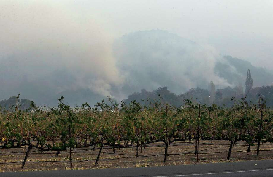 Plumes of smoke rise from a mountain behind a vineyard at Chateau St. Jean in Kenwood, Calif., Tuesday, Oct. 10, 2017. (AP Photo/Jeff Chiu) Photo: Jeff Chiu, STF / Copyright 2017 The Associated Press. All rights reserved.