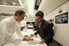 In this photo taken Thursday, March 9, 2017, chef Thomas Keller, left, describes a dish to a server in the new kitchen at the French Laundry restaurant in Yountville, Calif. At right on the wall is a closed-circuit video screen displaying the kitchen of Keller's sister restaurant Per Se in New York City. Keller has just opened a state-of-the art new kitchen at his famed French Laundry after spending $10 million on an extensive renovation.  (AP Photo/Eric Risberg)