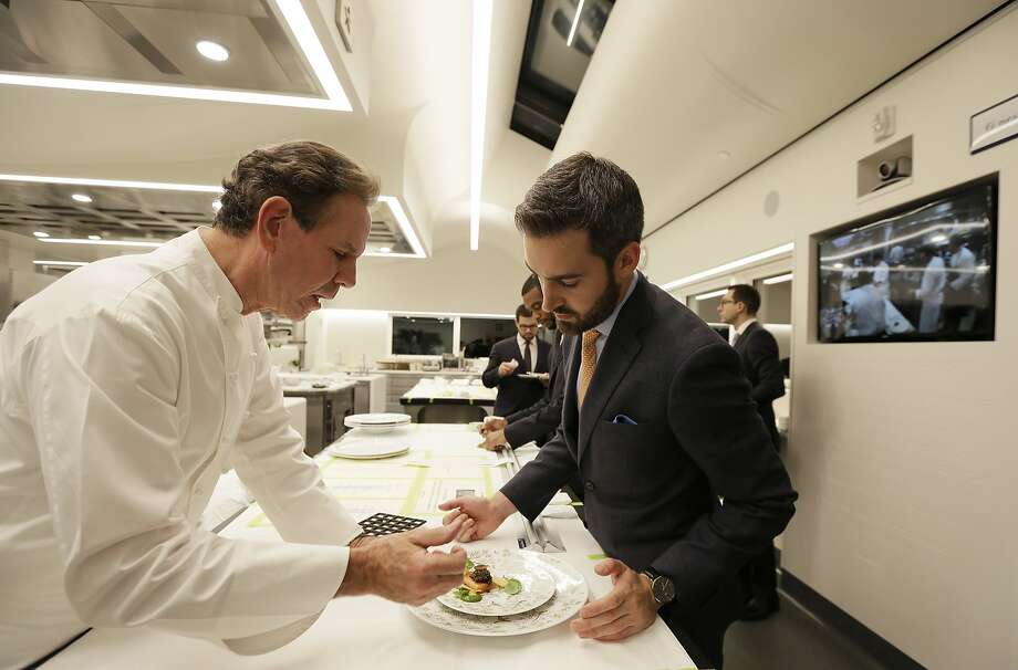 In this photo taken Thursday, March 9, 2017, chef Thomas Keller, left, describes a dish to a server in the new kitchen at the French Laundry restaurant in Yountville, Calif. At right on the wall is a closed-circuit video screen displaying the kitchen of Keller's sister restaurant Per Se in New York City. Keller has just opened a state-of-the art new kitchen at his famed French Laundry after spending $10 million on an extensive renovation.  (AP Photo/Eric Risberg) Photo: Eric Risberg, Associated Press