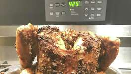 Bundt Pan Roast Chicken with Potatoes. The chicken sits upright during cooking, with the cone of the Bundt pan inserted into the cavity to stabilize it.