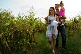 Irma and Dylan Rogers maneuver through the Tomball Corm Maze with one of their daughters.
