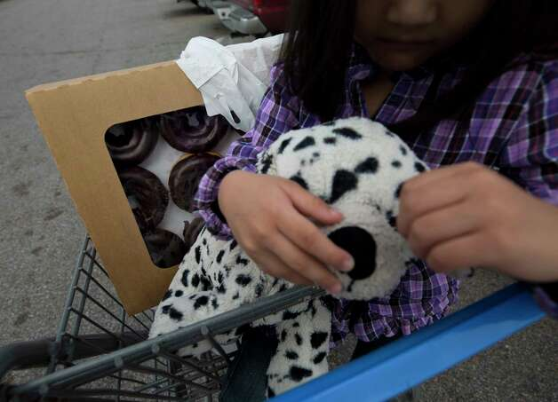 Ilem holds her puppy plush toy as her family walks back to their car after grocery shopping Saturday, Oct. 7, 2017, in Houston. Ilem convinced her mom, Rubi, on purchasing a dozen donuts, a big treat as the family is cutting back on expenses. Photo: Godofredo A. Vasquez, Houston Chronicle / Godofredo A. Vasquez