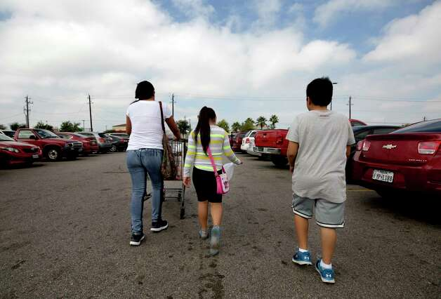 Rubi, left, to right, and her daughter Alin Ashley and son Ian walk back to their car after grocery chopping Saturday, Oct. 7, 2017, in Houston. Photo: Godofredo A. Vasquez, Houston Chronicle / Godofredo A. Vasquez