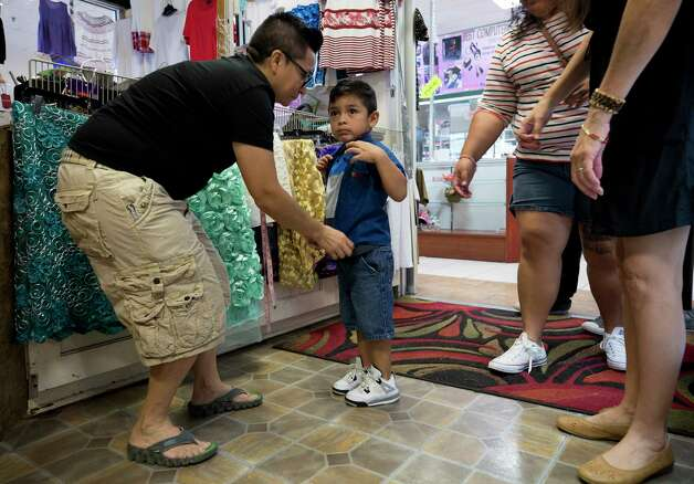 Emilia Alvarez, left, checks to see if the adjustments made to a shirt fit Kaleb Basurto, 3, inside E-Mily's Boutique Sunday, Oct. 1, 2017, in Houston. Photo: Godofredo A. Vasquez, Houston Chronicle / Godofredo A. Vasquez