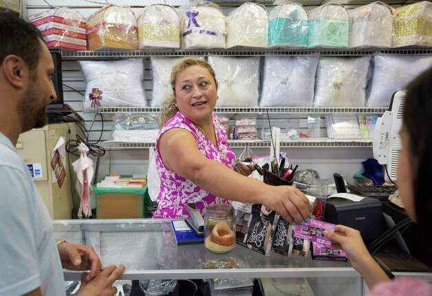Lety Alcocer, center, talks to customers Crispin, left, and Angelina Andrade inside Lety's Quinceañeras store Saturday, Oct. 7, 2017, in Houston. Alcocer has been in business 12 years, and said SB-4 and anti-emigrant rhetoric are hurting her once thriving business. Photo: Godofredo A. Vasquez, Houston Chronicle / Godofredo A. Vasquez