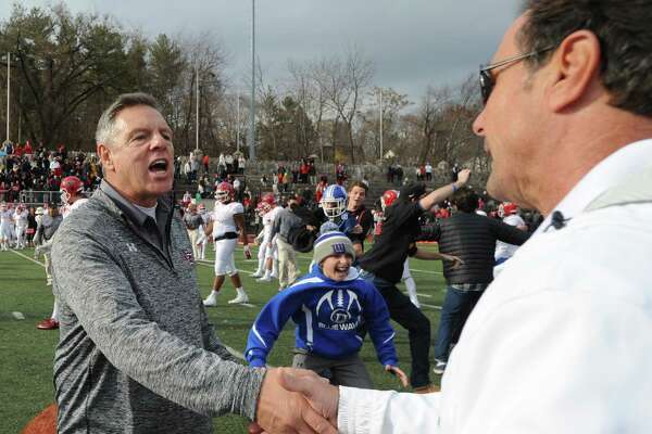 Lou Marinell, right, shakes hands with Rob Trifone. FCIAC Championship football game between New Canaan High School and Darien High School at Stamford High School's Boyle Stadium on Nov. 26, 2015. Darien took the championship Turkey Bowl title over New Canaan by a score of 28-21.